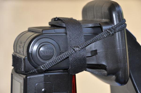 Black elastic bands keep O-Flash snug to speedligh...
