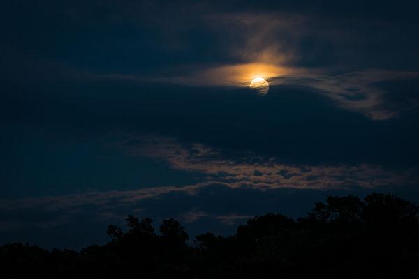 Full super moon peeking through the clouds...