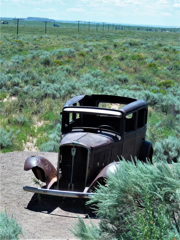 Old car parked in the sagebrush...