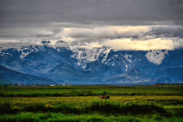 Eyjafjallajokul Glacier across fertile farmland in...
