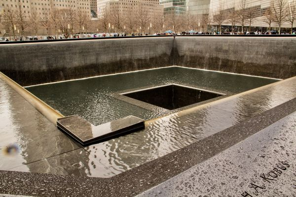 Hundreds of people surround the reflecting pool, a...