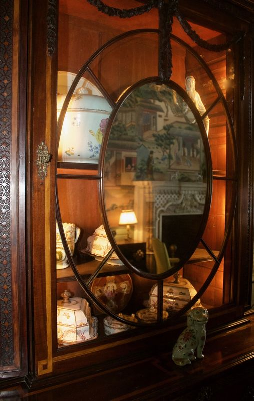 Old cabinet with oval miror reflecting the firepla...