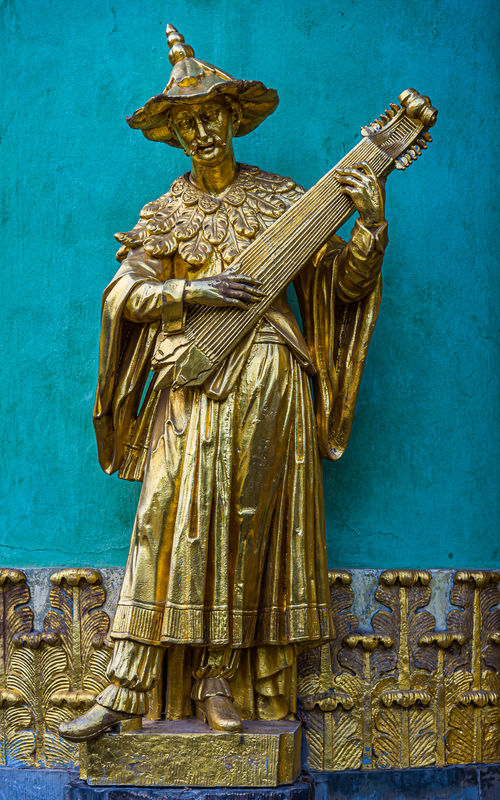 9 - Statue of a musician with a string instrument...