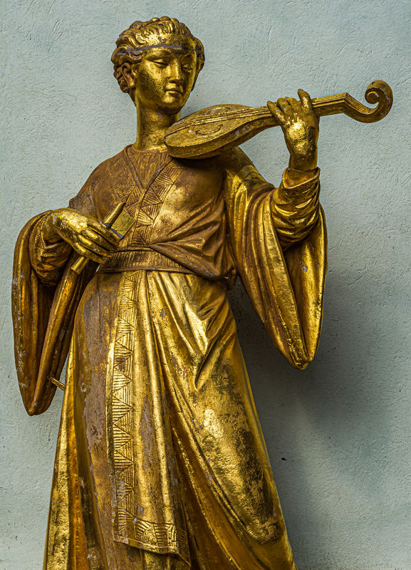 10 - Statue of woman with a string instrument...
